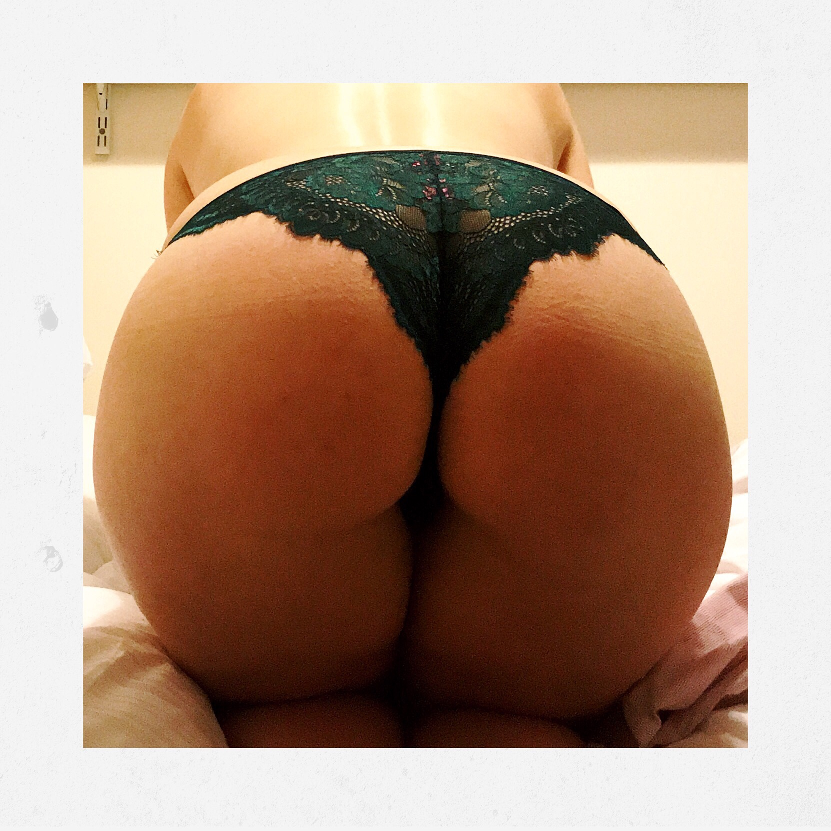 A photo of my arse bent over a bed, wearing green lacy pants