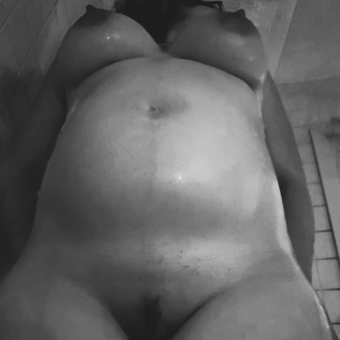 A black and white image of my 28 week pregnant body, seen from below as I stand up from the bath.