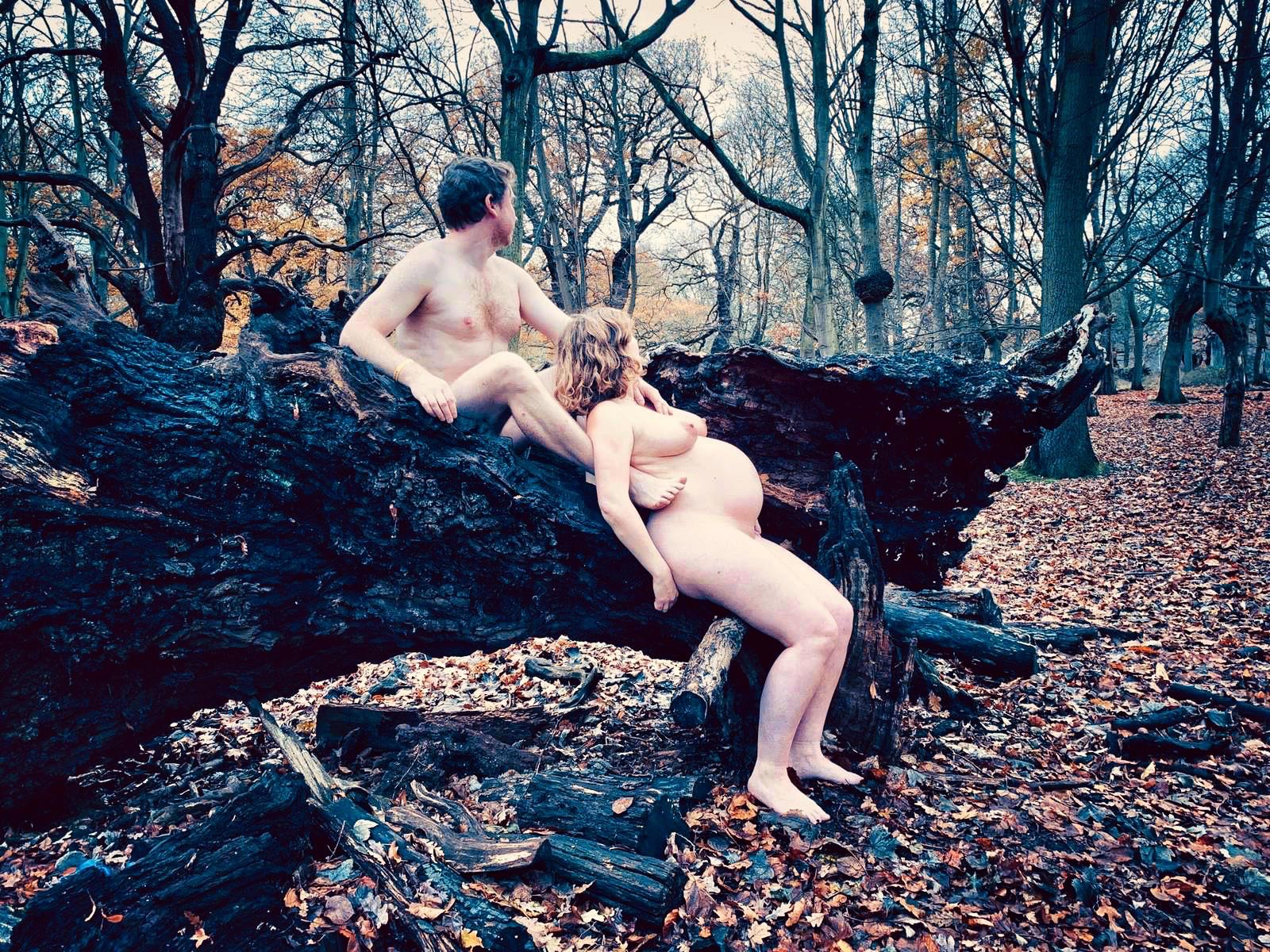EA and I are sat naked on a large log in the woods, in profile and facing away
