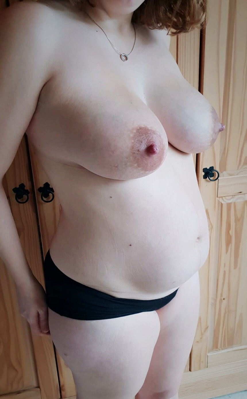 A half profile picture of my 1 week postpartum body. My belly is soft with visible stretch marks and my breasts look swollen with enlarged nipples and visible veins.