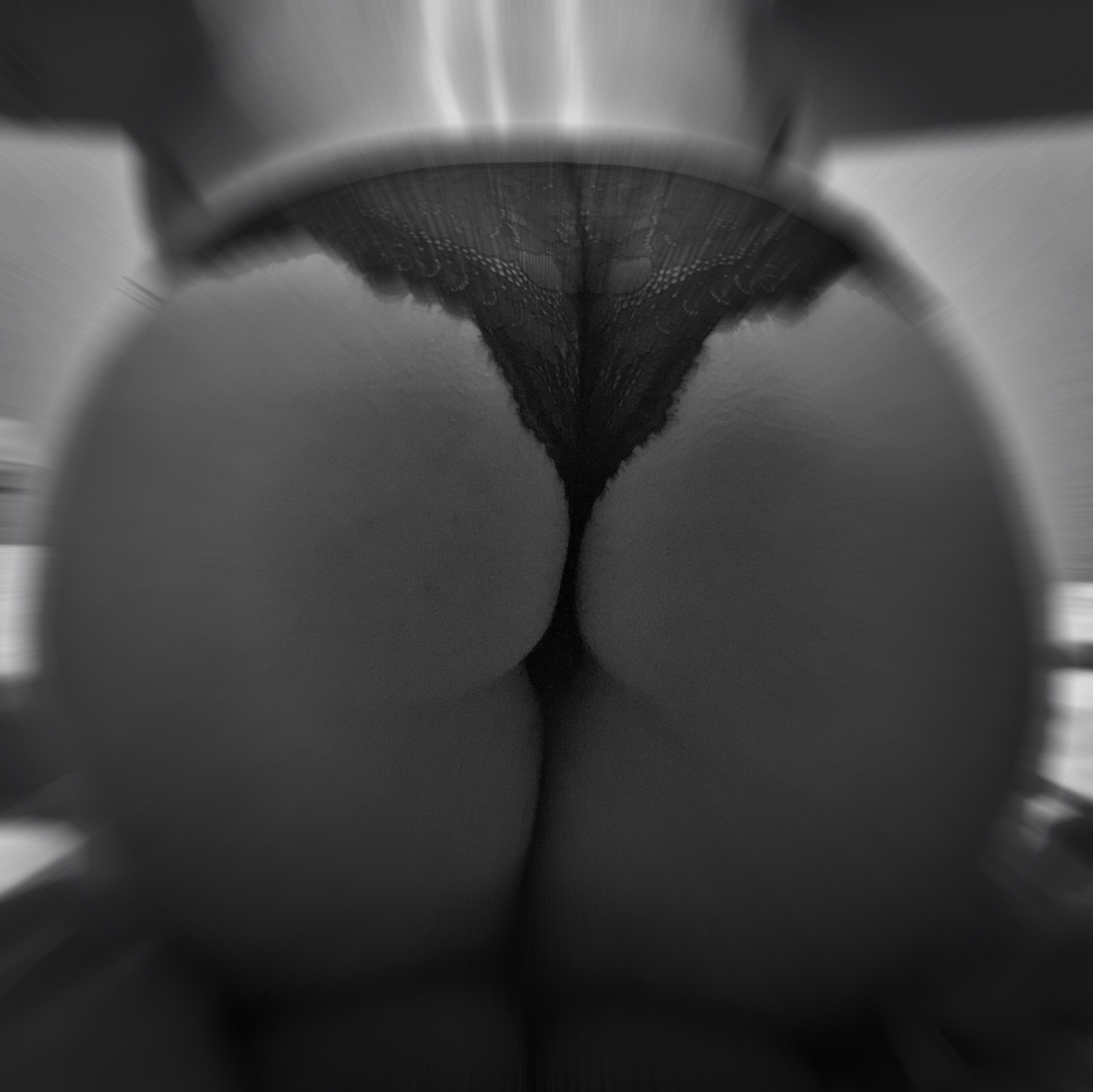 A photo of my arse as I bend over a bed in black and white, wearing lacy pants