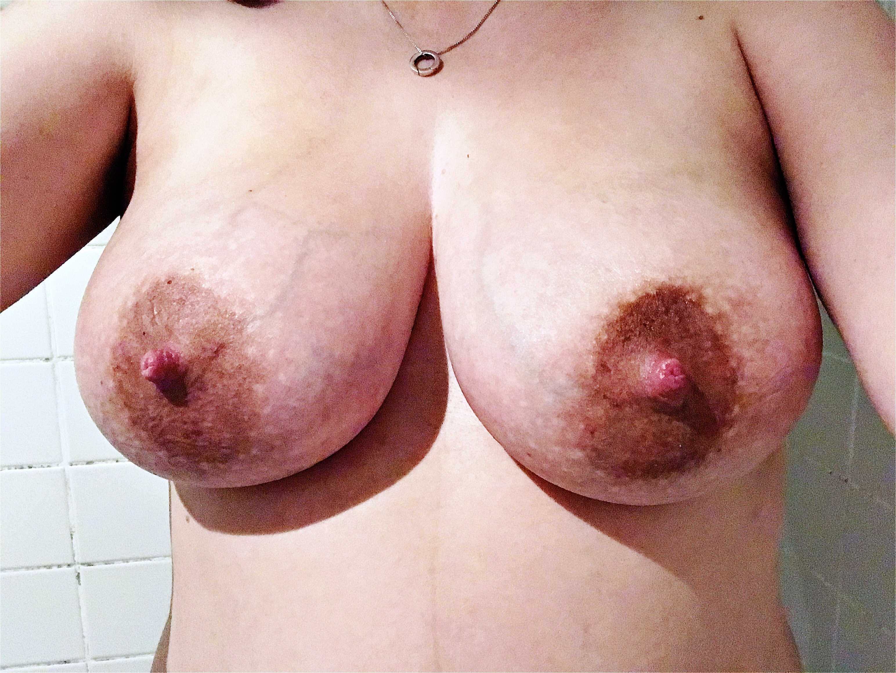 An image of my breasts, standing almost directly facing the camera against a white tiled background