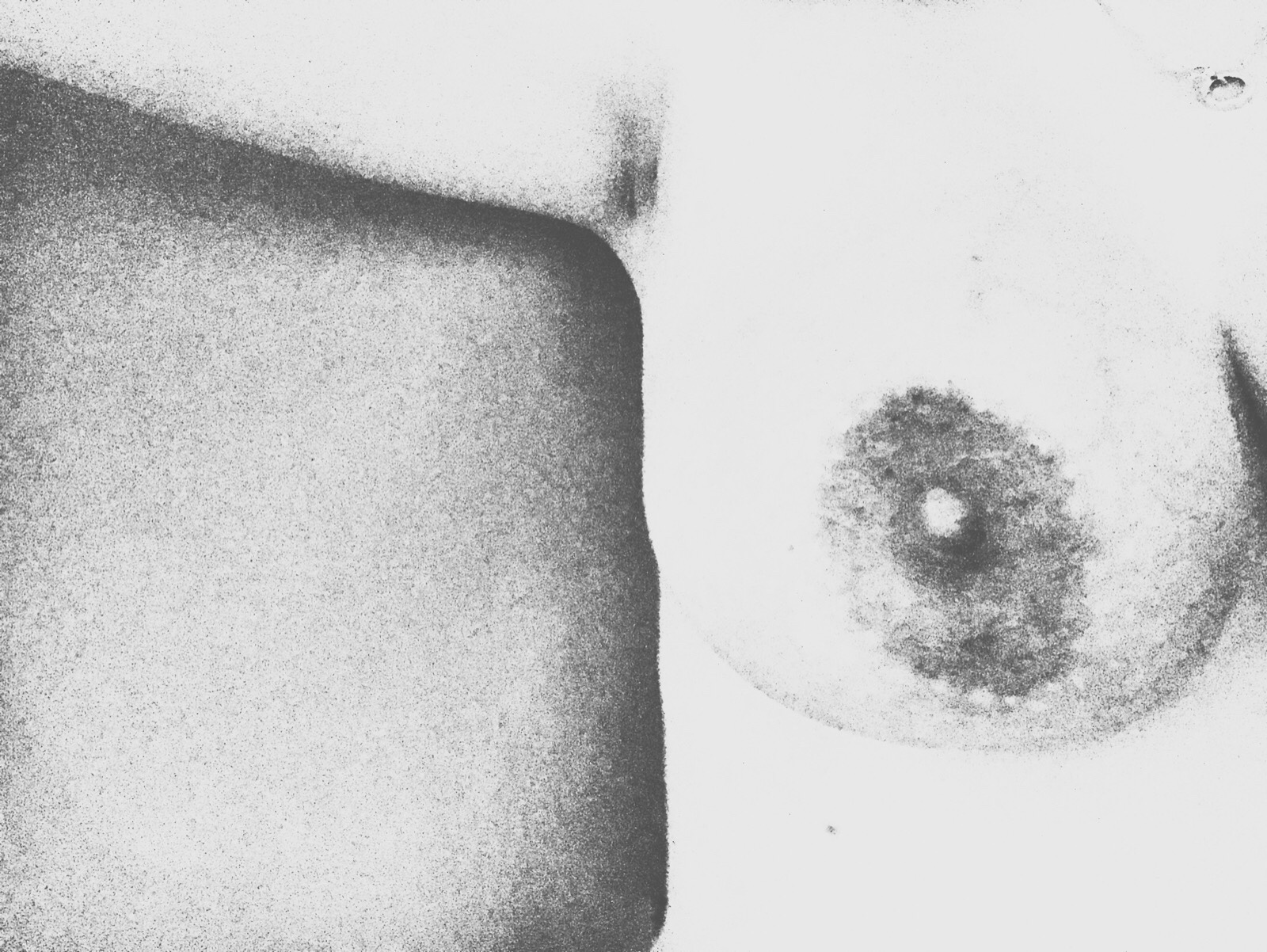 An image of my right breast with arm stretched out at right angles along the top of the image, washed out by a black and white filter