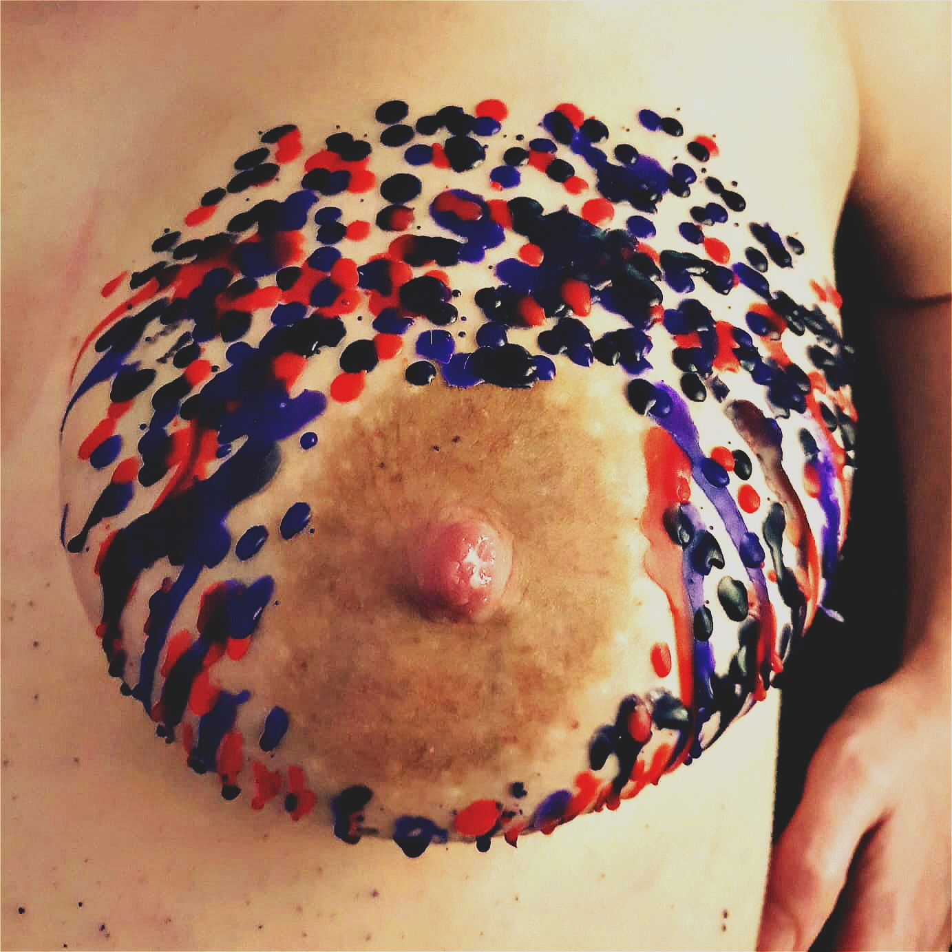 A photo of my left breast, decorated with drips of black, purple and red wax