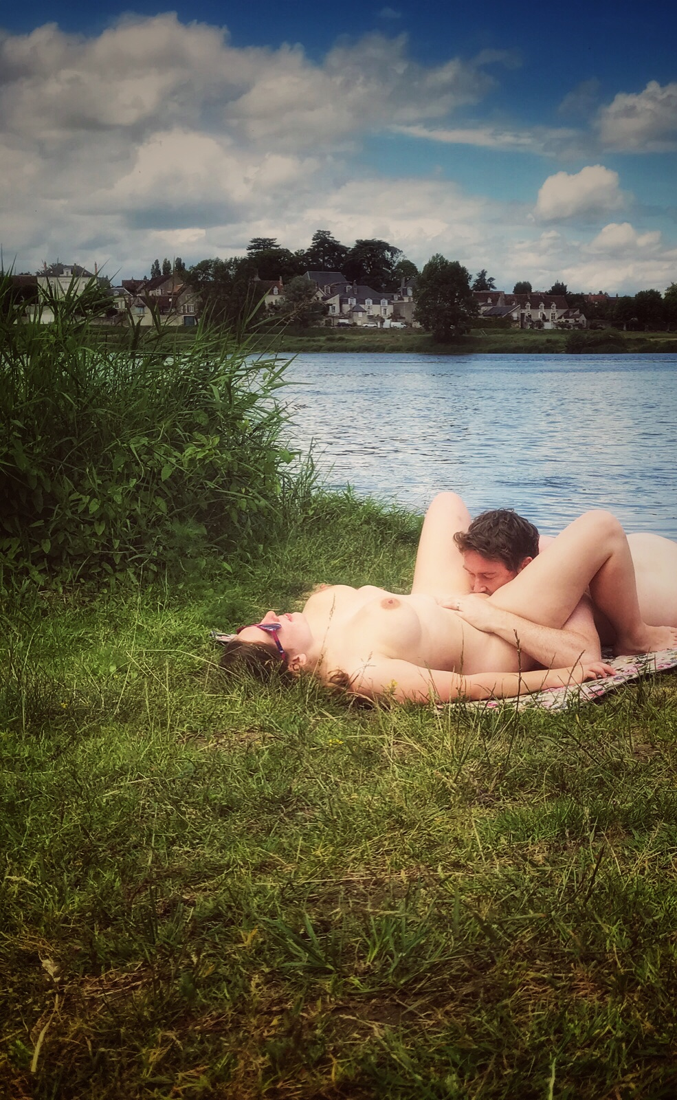 A photo of EA and I, lying naked on a picnic blanket by a river. I am on my back, he is going down on me