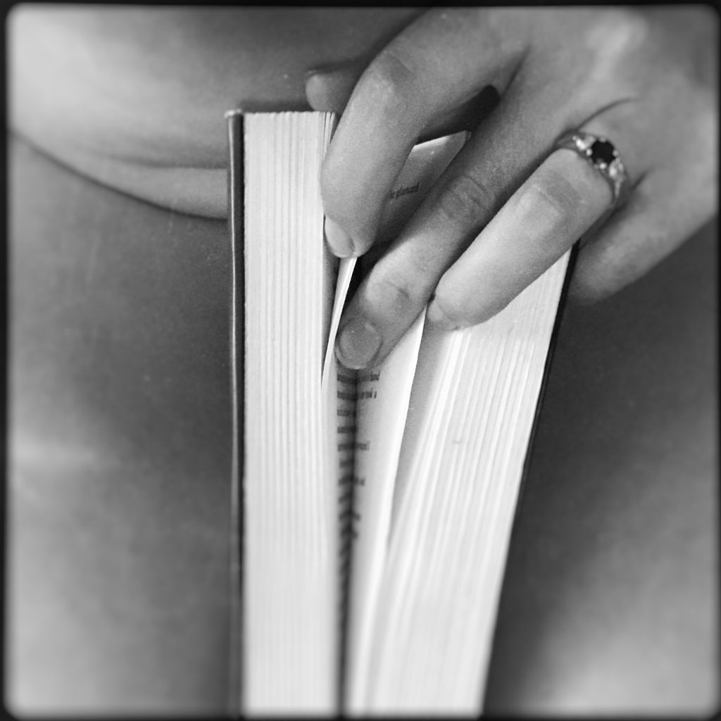 Read my lips: A black and white image of me, holding a book between my thighs and fingering the pages