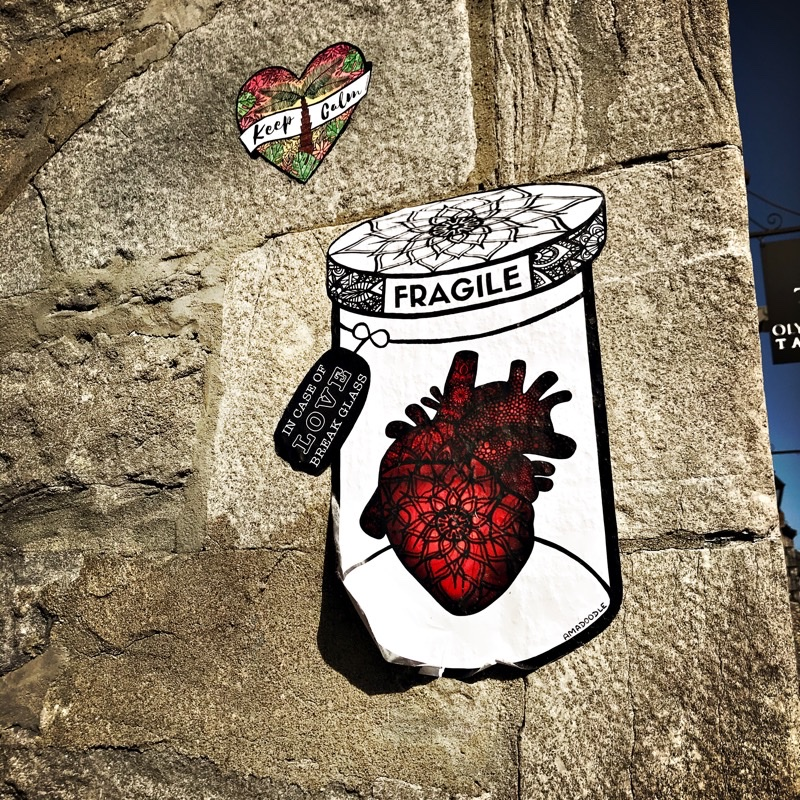 Graffiti showing a heart inside a glass jar with a label 'Fragile. In case of love, break glass.'