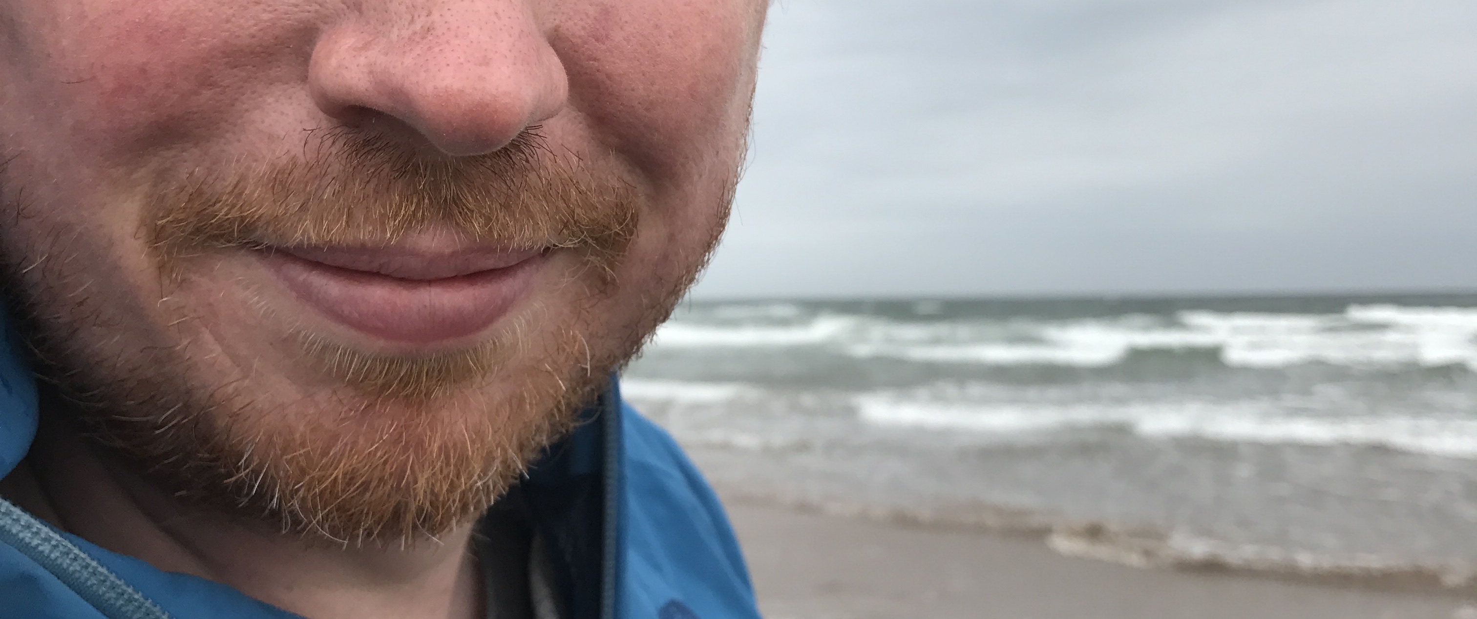 A photo of EA's mouth and chin, smiling by the sea