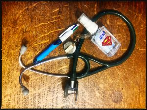 A photo of a pen,  stethoscope and small bottle of Purell, labelled with a Superman S. Superheroes