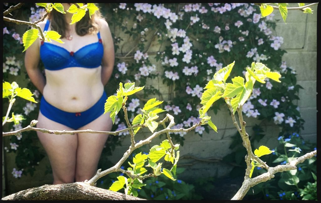 A photo of me, in my blue underwear, seen through the leaves of a tree