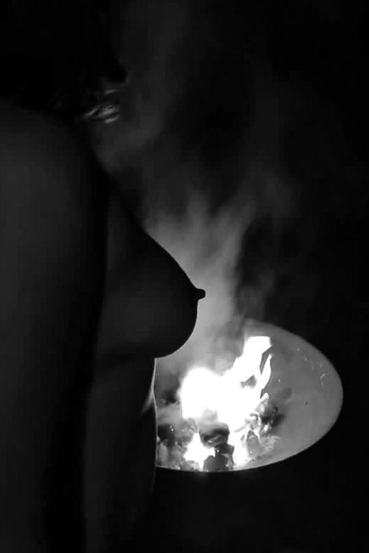 A black and white silhouette of my breast, outlined against fire of a fire pit