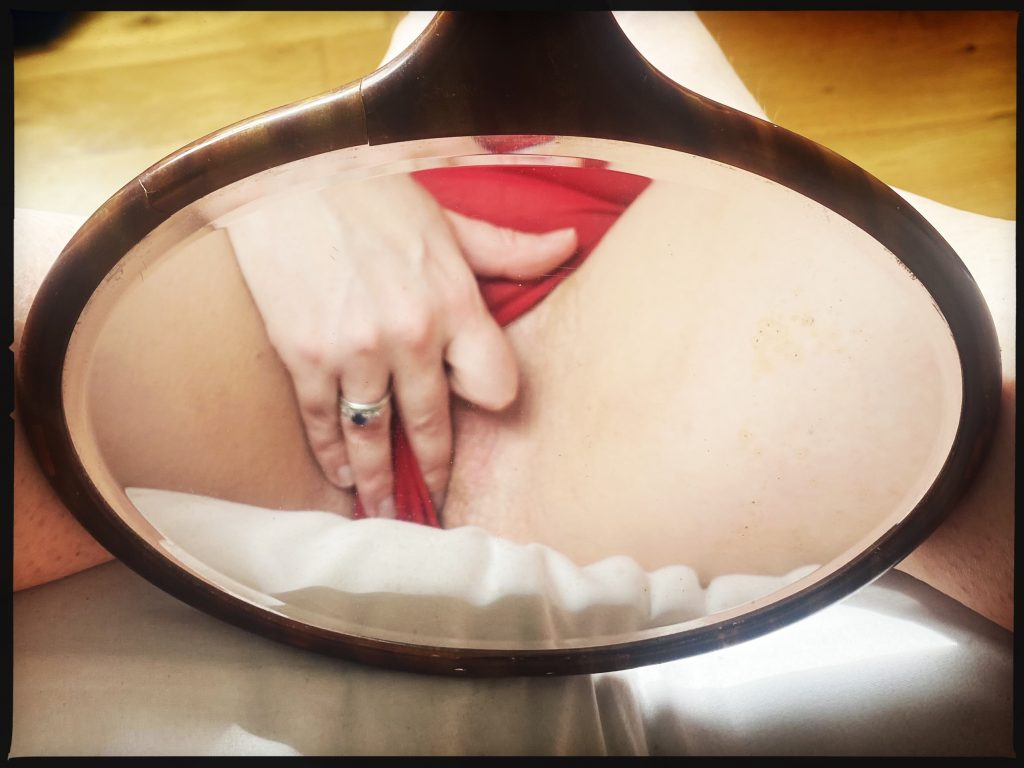 A photo of my reflection in a hand mirror, showing my red underwear and my fingers slipping beneath them...